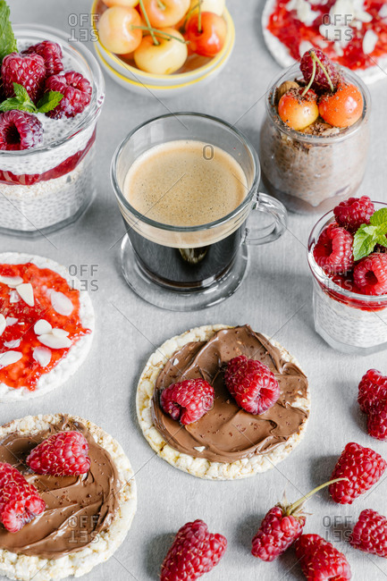 High angle of glass cup of coffee with chia pudding garnished with raspberries and white cherries with wheat crispbreads with nut spread and jam with almond pieces