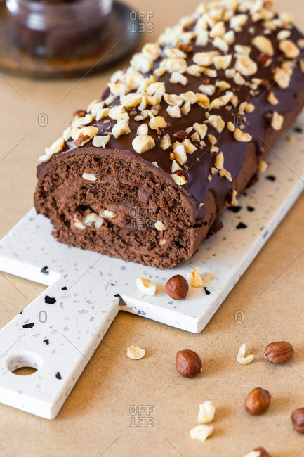 Delicious homemade roll cake with chocolate glaze and hazelnut placed on chopping board in modern kitchen