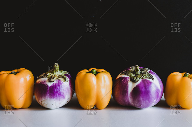 Fresh yellow peppers and eggplants placed in line on table on black background in studio
