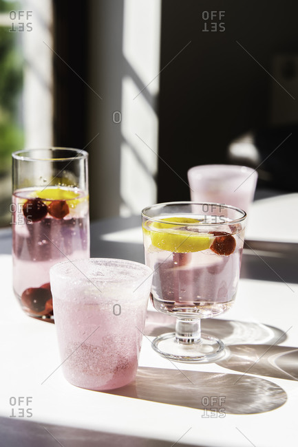 Fresh detox water with cherry and mint placed on table lit by sun in modern apartment
