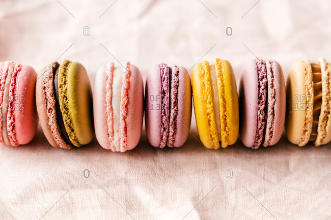 Closeup of assorted delectable macarons placed on pink table
