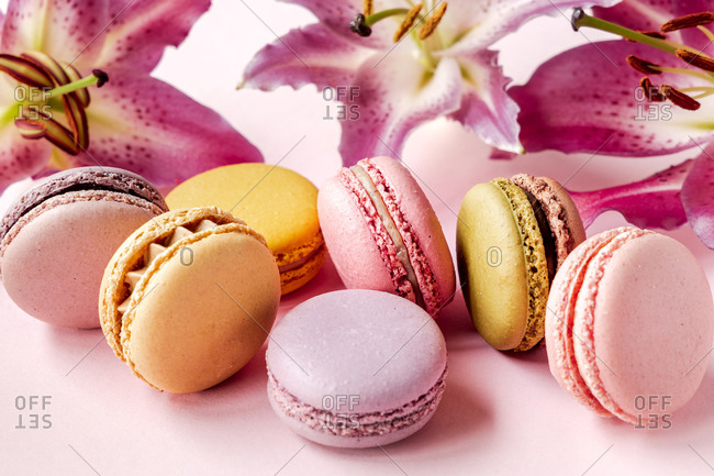 Closeup of assorted delectable macarons placed on pink table with fresh lily flowers