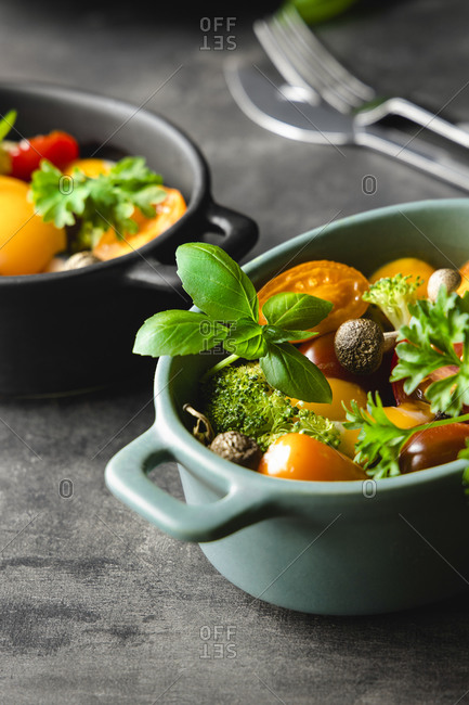 From above of tasty vegetable salad with tomatoes and mushrooms garnished with green basil and rosemary sprigs placed in bowls on table in kitchen