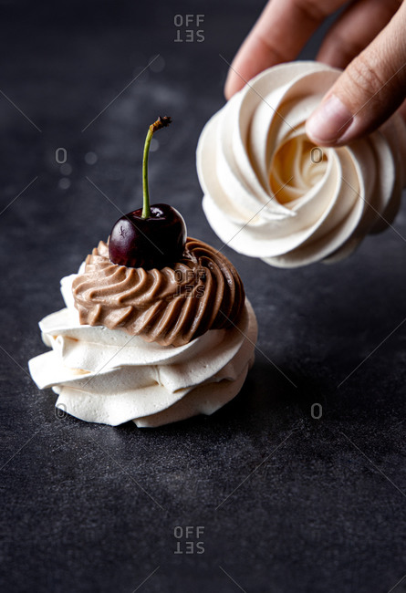 Crop female with delicious Pavlova meringues with chocolate cream and fresh cherry on black table