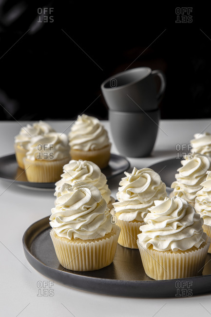 Tasty vanilla cupcakes with sweet cream placed on tray on table on black background