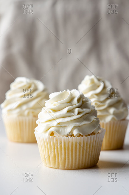 Tasty vanilla cupcakes with sweet cream placed on tray on table on white background
