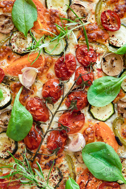 From above of palatable vegetarian pizza with cherry tomatoes and mushrooms garnished with fresh basil and rosemary