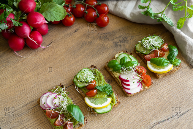Top view of delicious toasts with radish and lemon slices garnished with basil sprigs and placed on wooden table in kitchen