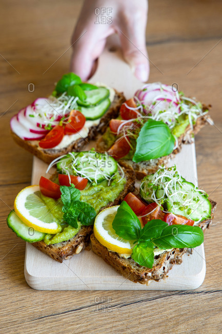 Crop female with delicious toasts with cucumbers and tomatoes garnished with fresh lemon and sprigs of basil and placed on wooden chopping board