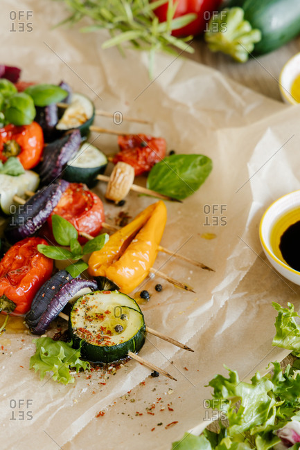 High angle of delicious grilled cucumbers and tomatoes on sticks placed on table with lettuce and sauce