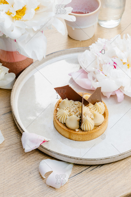 High angle of palatable caramel tart garnished with white and milk chocolate and placed on tray with peony flowers