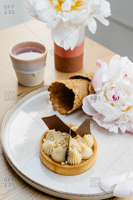 High angle of palatable caramel tart garnished with white and milk chocolate and placed on tray with waffle cones and peony flowers