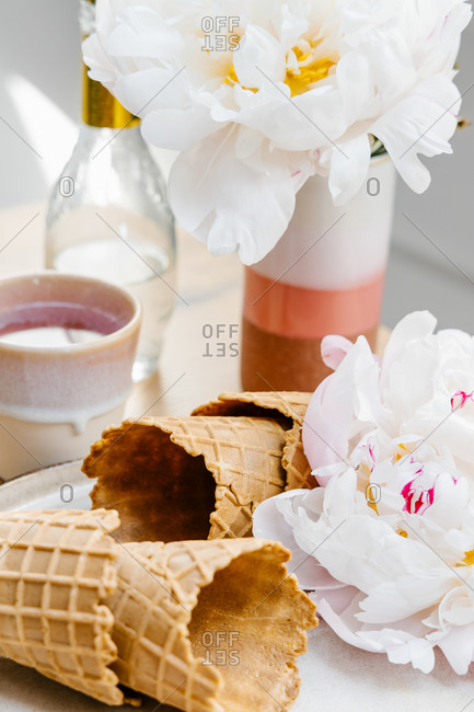High angle of crispy waffle cones placed on tray with peony flower on wooden table