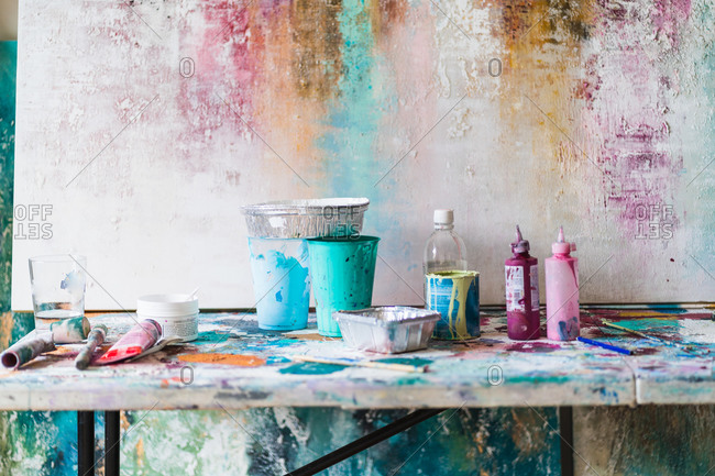Plastic bottles with colorful paints and empty containers near artist tools on dirty table near multicolored wall with uneven surface in art studio
