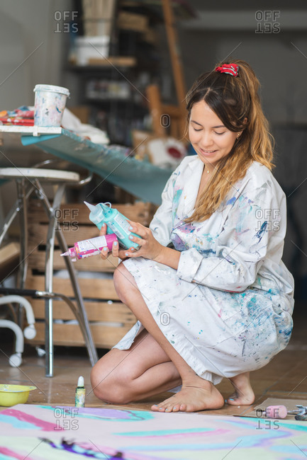 Smiling barefoot female in dirty robe squatting on wooden floor holding plastic bottle with paints while looking at abstract picture in art studio