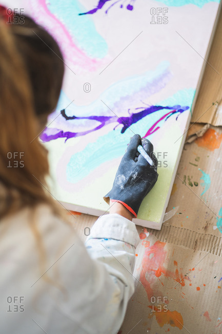 Crop anonymous female illustrator in dirty robe and gloves sitting on floor with paintbrush in front of palette with gouache paints in workshop