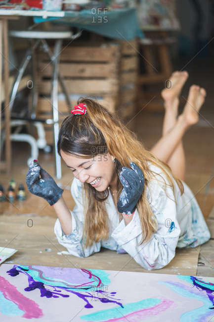 Cheerful barefoot female artist in dirty robe and gloves lying on wooden floor with closed eyes in front of abstract painting in art studio