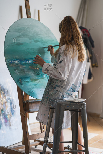 Side view of unrecognizable focused female master in dress smeared with paint painting seascape with paintbrush on round canvas fixed on wooden easel in art studio