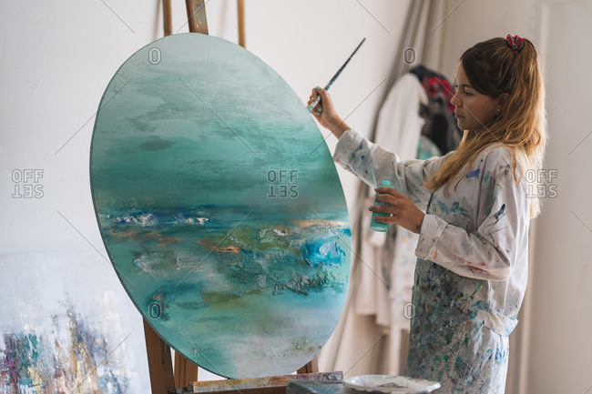 Side view female master in dress smeared with paint painting seascape with paintbrush on round canvas fixed on wooden easel in art studio
