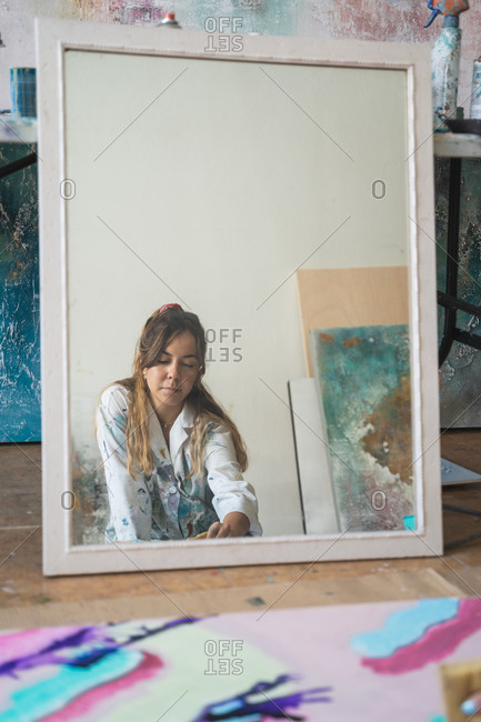 young female artist reflected in mirror painting creative picture with paintbrush and colorful paints on canvas board placed on floor in art studio
