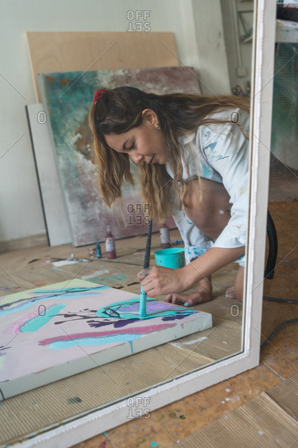 Side view of young female artist reflected in mirror painting creative picture with paintbrush and colorful paints on canvas board placed on floor in art studio
