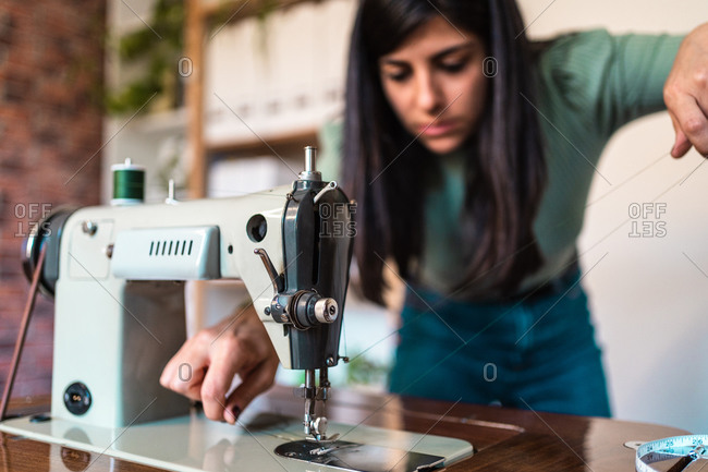 Crop serious ethnic craftswoman extending thin thread while using modern metal sewing machine with spool on top on wooden table in workshop