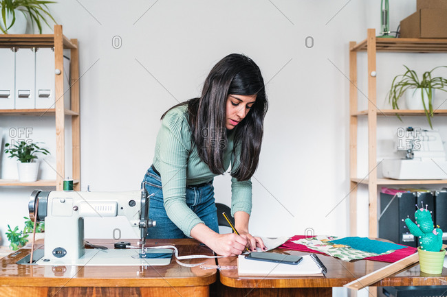 Ethnic female tailor in casual wear taking note on sheet of paper while leaning forward near sewing machine and blank notepad with fabric samples in workshop