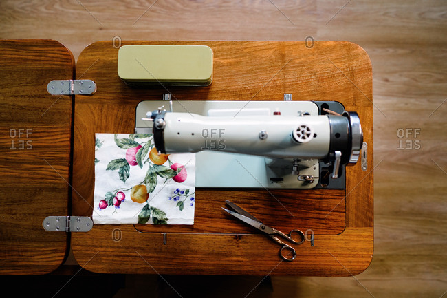 From above of composition of professional metal sewing machine and square textile sample with leaves and fruits pattern near sharp scissors in atelier