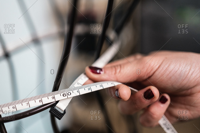 Cropped unrecognizable seamstress taking measurements of wire dummy standing in loft style studio
