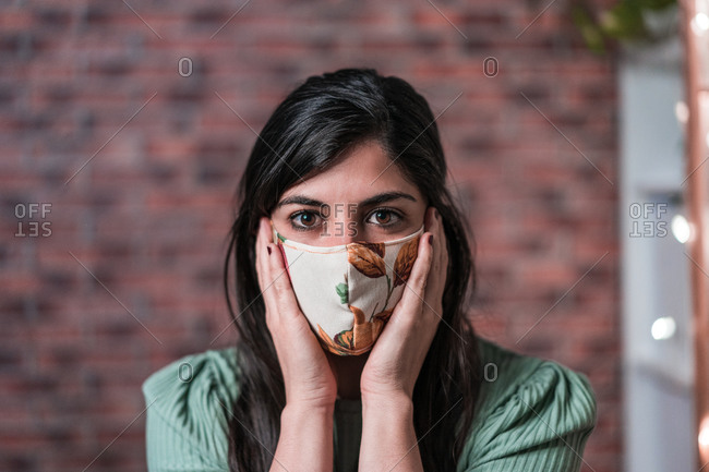 Craftswoman testing green pattern handmade face mask for protection during coronavirus pandemic while creating masks in loft style workshop