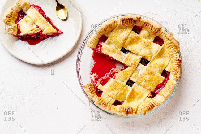 Sweet pie with apples and cranberries decorated with lattice with one slice cut.