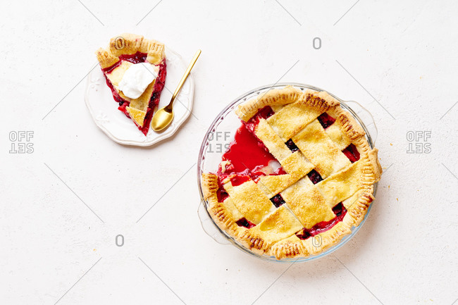 Sweet pie with apples and cranberries decorated with lattice. One slice cut and served with cream.