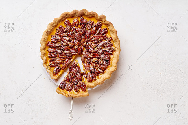 Overhead image of pecan pumpkin tart with one slice cut