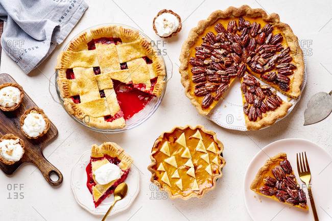 Top view shot of variety of thanksgiving pies: berry pie, pumpkin pie and pecan tart