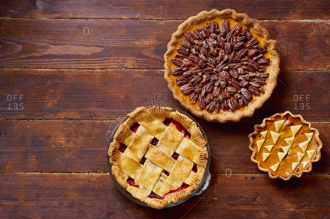 Variety of thanksgiving pies on wooden table.