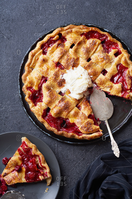 Top view image of cherry pie decorated with lattice and served with ice cream