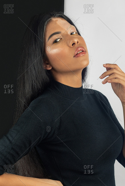 Young sensual emotionless ethnic female with dark hair and vitiligo skin condition looking at camera while standing near black and white wall in flat