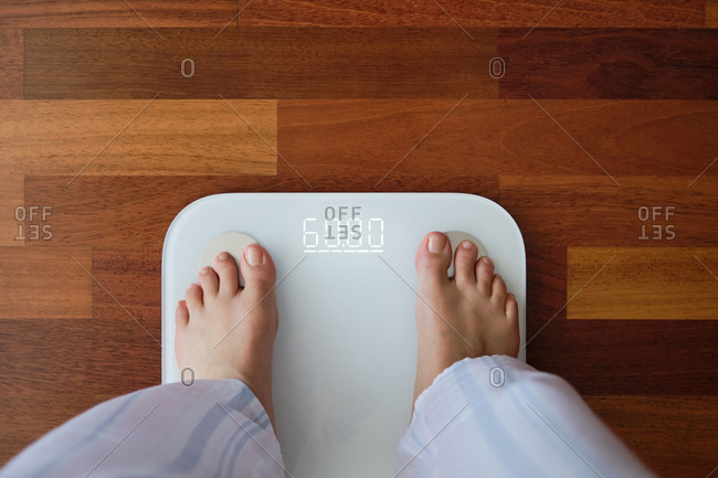 Top view crop faceless barefoot female in cozy pajama standing on digital weight and body fat scales with display showing healthy weight of 60 kg on bathroom floor in morning
