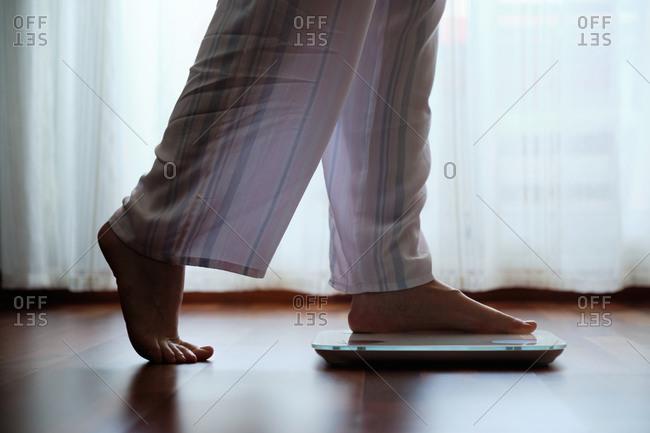 Crop faceless barefoot female in cozy pajama standing on digital weight and body fat scales with display on bathroom floor in the morning