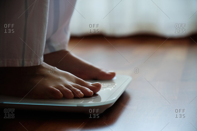 Crop faceless barefoot female in cozy pajama standing on digital weight and body fat scales with display showing healthy weight of 60 kg on bathroom floor in morning