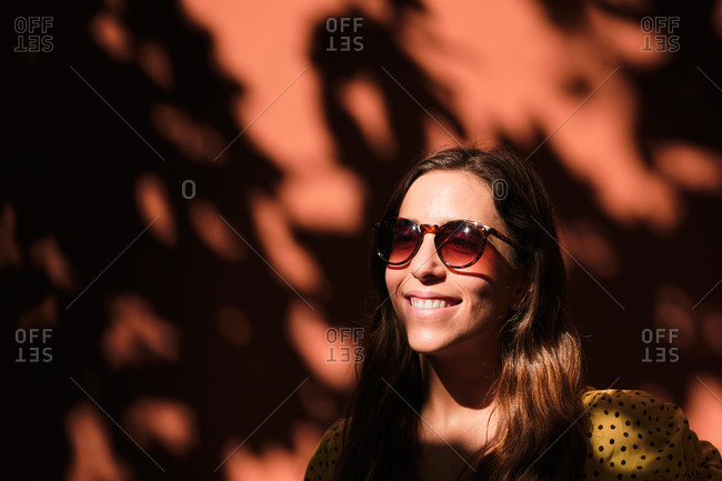 Charming female in summer dress standing in shadow of tree near stone building and enjoying sun during city stroll looking away