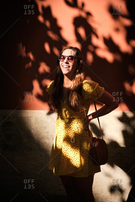 Charming female in summer dress standing in shadow of tree near stone building and enjoying sun during city stroll
