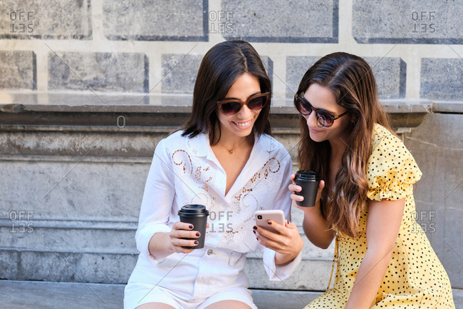 Smiling female friends with coffee to go sitting in city and browsing mobile phone together while chatting on social media