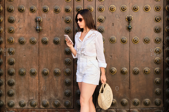 Calm female in summer wear standing near ornamental gates on street and reading messages during stroll in summer