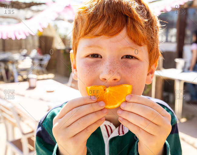 Little preteen redhead boy with freckles in casual clothes eating a slice of a orange and looking at camera