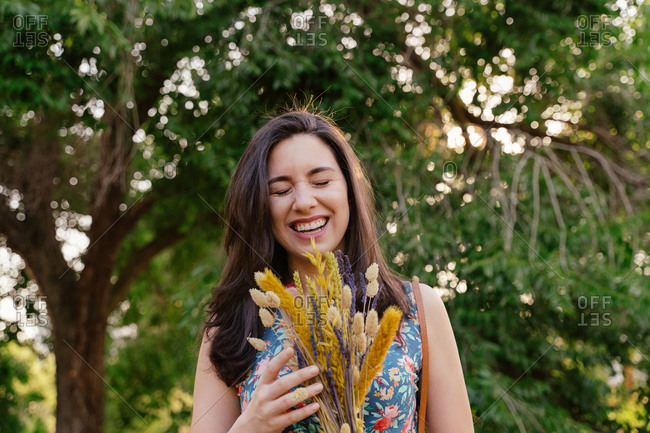 Cheerful young female in summer dress holding bouquet of wildflowers and laughing happily while enjoying sunny spring day in nature