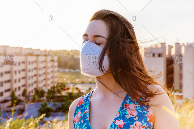 Young female in casual dress and protective mask for coronavirus prevention standing against blurred urban background in sunny summer evening