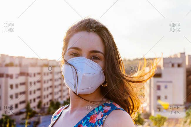 Positive young female in casual dress and protective mask for coronavirus prevention looking at camera and smiling while standing against blurred urban background in sunny summer evening