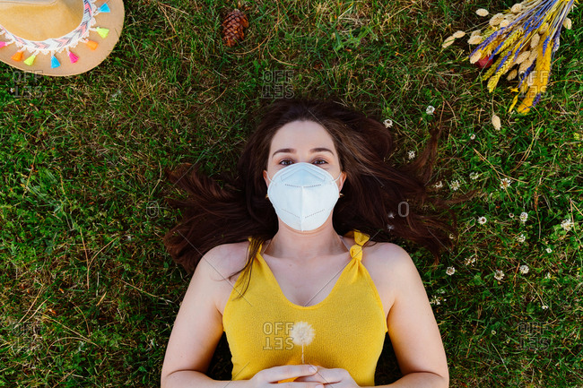 From above of calm female in summer wear and protective mask relaxing on green meadow while enjoying weekend and looking at camera during coronavirus outbreak
