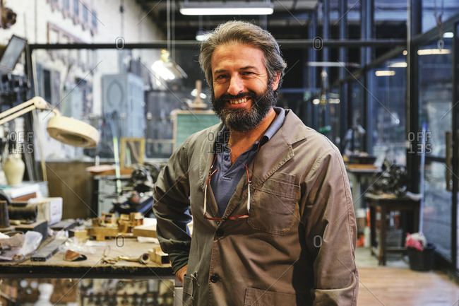 Happy middle aged bearded craftsman in robe with hanging eyeglasses standing and looking at camera in studio